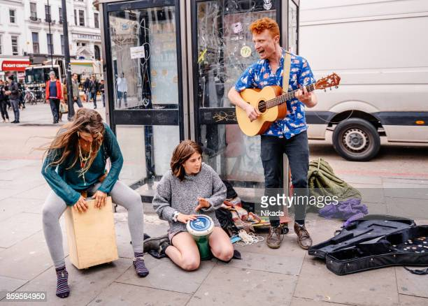 street musicians playing music in city of london, england - busker stock pictures, royalty-free photos & images