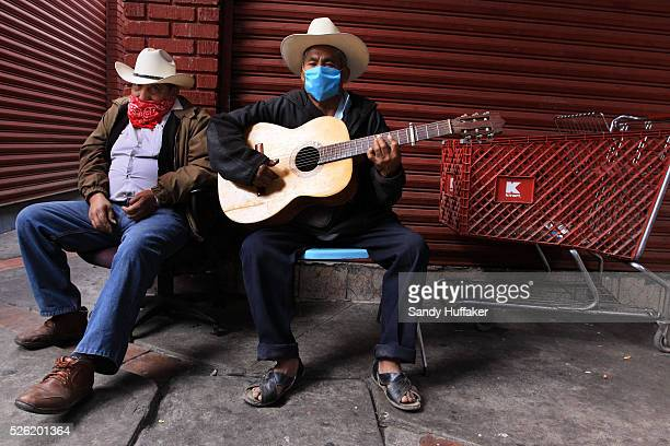 Street musicians wait for work while wearing a surgical mask at a market near the Mexico-U.S. Border at the Port of Entry in Tijuana, Mexico. The...