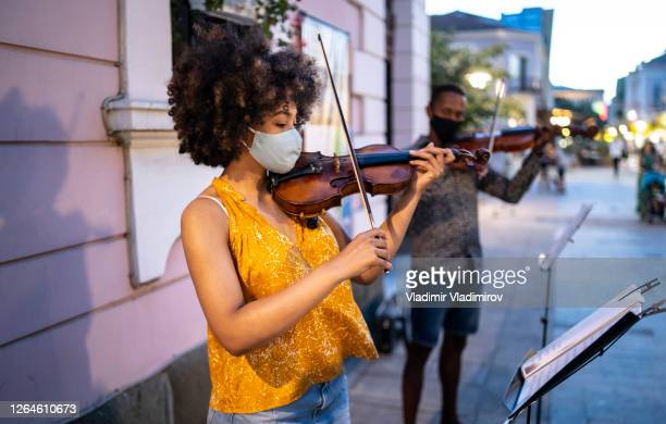 street musicians wearing face masks playing music in time of pandemic - musician stock pictures, royalty-free photos & images