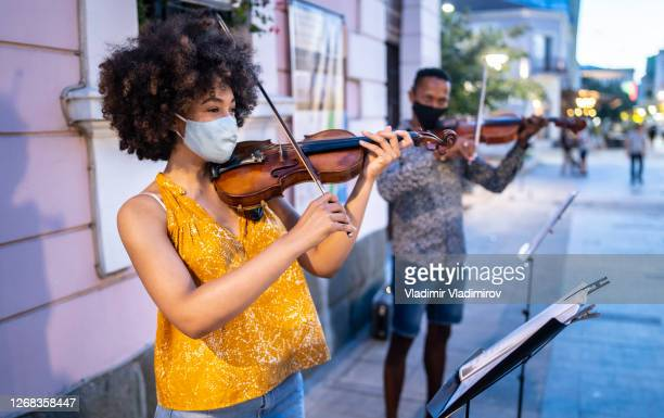 street musicians wearing face masks playing music in time of pandemic - street artist stock pictures, royalty-free photos & images
