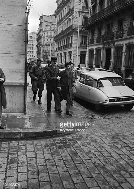 A street of Algiers a policeman aided by soldiers arrests an Algerian suspect