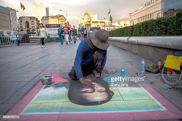 A street painter draws a Mona Lisa Smile with chalk on the ground in downtown square At the turn of the 20th century Harbin grew into the largest...