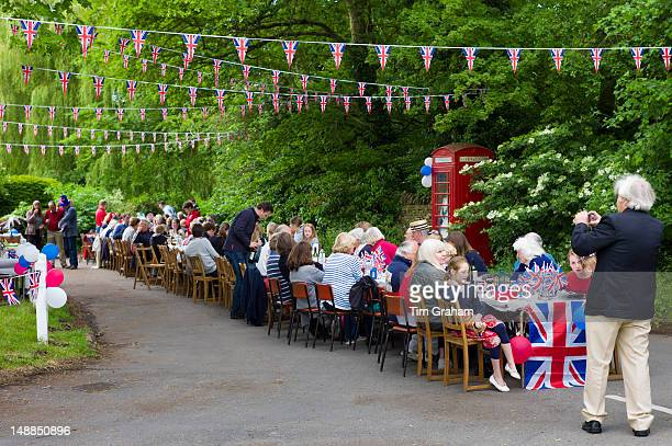 Street party with Union Jack flags and bunting to celebrate Queen's Diamond Jubilee at Swinbrook in The Cotswolds UK