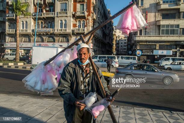 Street pedlar sells cotton candy along the corniche by the Mediterranean waterfront in Egypt's northern city of Alexandria on March 26, 2021.