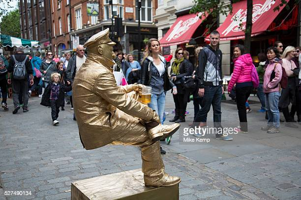 Street performer as a metallic painted balancing 'Living Statue' in Covent Garden delighting the gathered crowds London UK