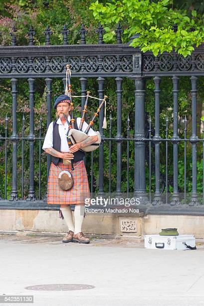 Street performer at downtown Toronto Man dressed in traditional Scottish kilt attire and playing the bagpipes