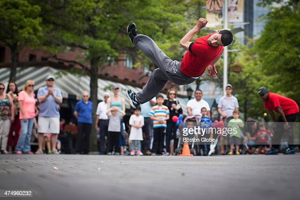 Street performer Bilel Sirer of the Yak Crew does a flip as he performs for tourists at Christopher Columbus Park in Boston Massachusetts May 25 2015