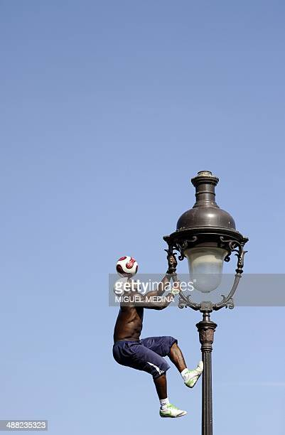 A street performer does acrobatics tricks with a soccer ball as he balances on an old style street light on July 31 2011 in Paris at the SacréCoeur...