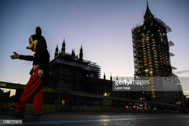 Street performer dressed as Mickey Mouse greets tourists as the sun sets over the Houses of Parliament on December 11, 2020 in London, England. The...