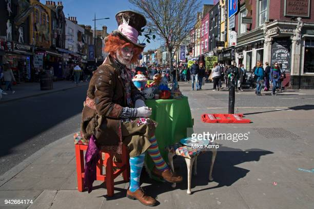 Street performer dressed up as the Mad Hatter from the Alice in Wonderland story sits at his table having his own Mad Hatter's tea party in Camden...
