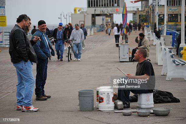 CONTENT] A street performer drums for an audience on a bleak February day at the Santa Monica Pier in Santa Monica California