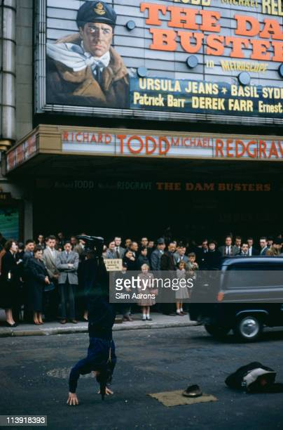 A street performer entertains the crowds queuing for the cinema in Leicester Square London 1955 The cinema is showing 'Michael Anderson's war film...