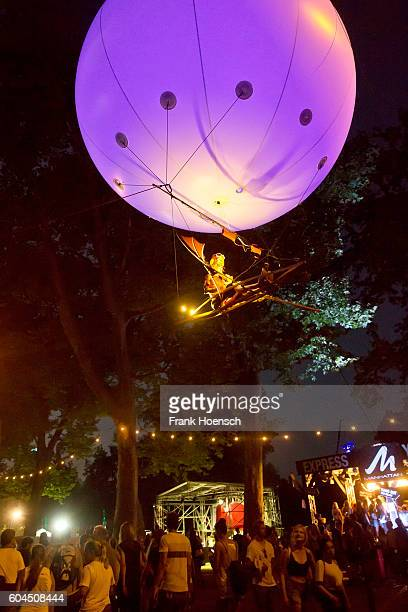 A street performer flies in a mockup balloon above visitors during the second day of Lollapalooza Festival at the Treptower Park on September 11 2016...