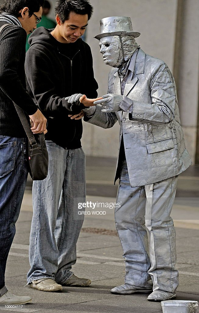 A street performer (R) interacts with two visitors to the Circular Quay tourist precinct near Sydney Harbour on May 19, 2010. Australian officials in March launched a new promotion under the slogan 'There is nothing like Australia', aimed at recapturing flagging tourist revenues. AFP PHOTO / Greg WOOD