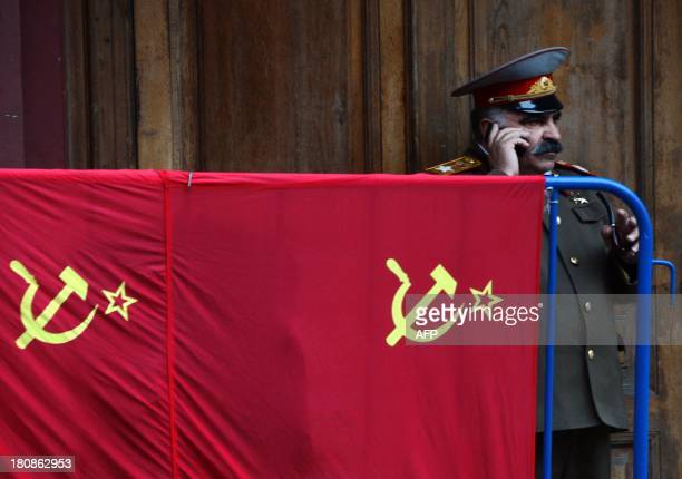 A street performer made up and dressed as Soviet dictator Josef Stalin uses his mobile phone a he stands near Soviet flags displayed for sale outside...