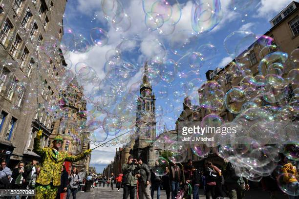 A street performer on the Royal Mile entertains members of the public with a mass of bubbles on May 27 2019 in Edinburgh Scotland