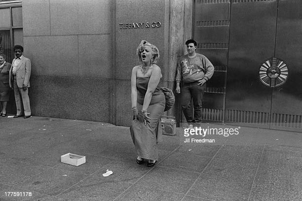 Street performer outside 'Tiffany & Co' sings along to a portable stereo, New York City, circa 1982.