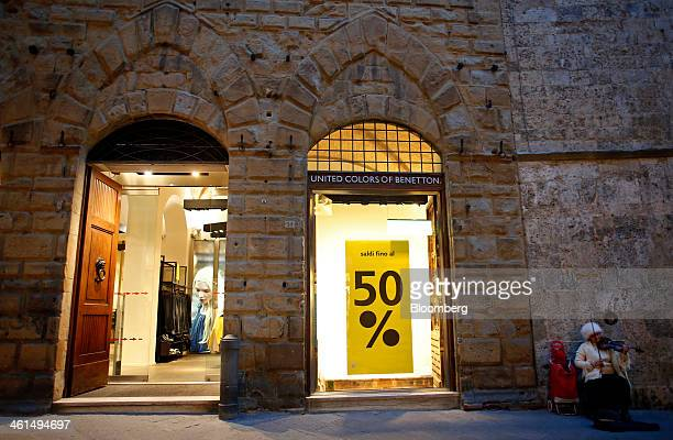 A street performer plays a violin near a Benetton store operated by Benetton Group SpA in Siena Italy on Wednesday Jan 8 2014 Banca Monte dei Paschi...