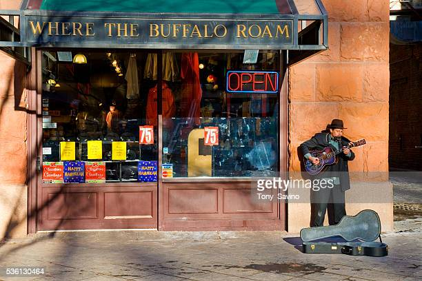 A street performer plays the guitar in front of a store called Where the Buffalo Roam at the 16th Street Mall