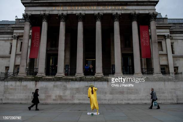 A street performer stands in front of the National Gallery in Trafalgar Square as the outbreak of coronavirus intensifies on March 15 2020 in London...