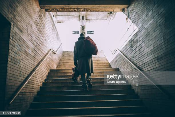 street performer walking up the steps - homelessness stock pictures, royalty-free photos & images