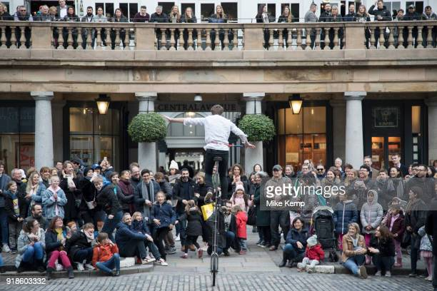 Street performer with a tall unicycle thrills the gathered crowd with his performance in Covent Garden London England United Kingdom