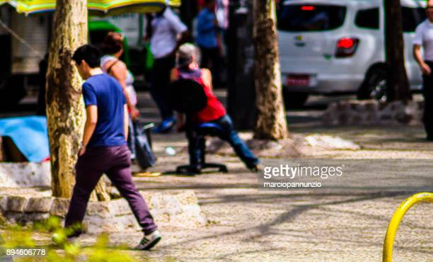 street photography documenting in an artistic way the urban daily life in the city of são paulo, brazil. selective focus. special lens, large aperture and tilt-shift built by the photographer. - sentar se imagens e fotografias de stock