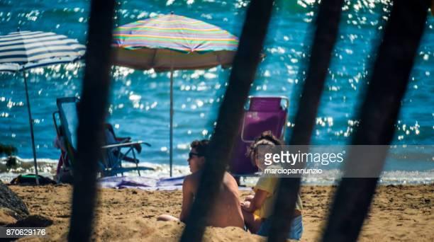 street photography documenting the daily life of the beach in ilhabela, brazil - sentar se imagens e fotografias de stock