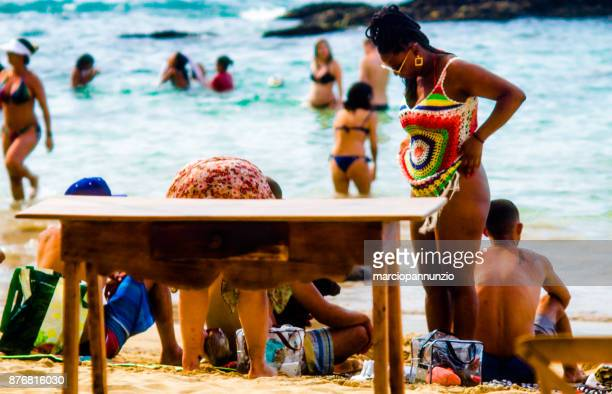 street photography documenting the daily life of the beach in ilhabela, brazil. - sentar se imagens e fotografias de stock