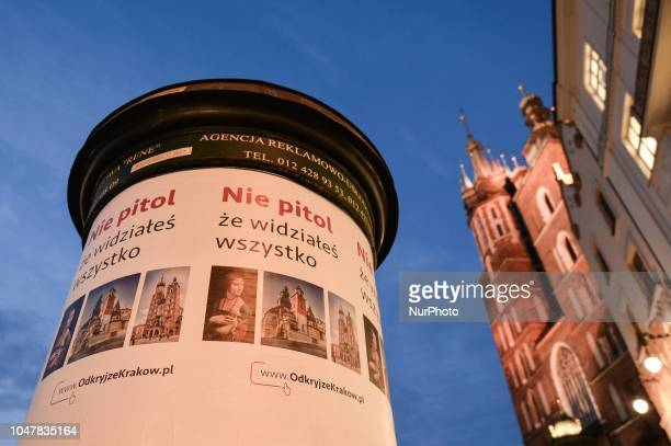 A street pillar with the city ads in front of Mariacki Basilica on the Main Market Square in Krakow's Old Town On Sunday October 7 in Krakow Poland