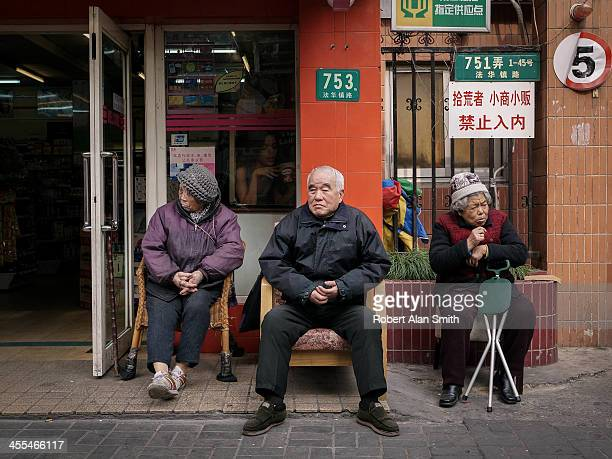 CONTENT] street portrait of 3 retired Chinese people sitting outside a shop on the streets of Shanghai The expressions and postures indicate that...