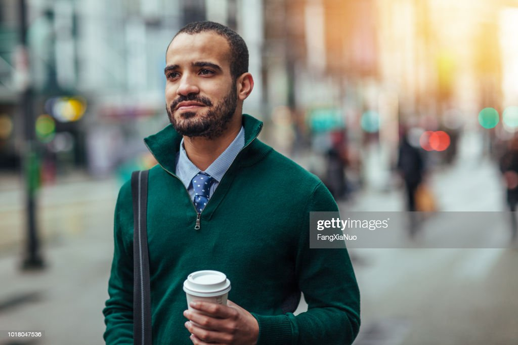 Street portrait of a young businessman holding a cup of coffee : Stock Photo