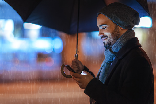 Street portrait of a young man holding mobile phone on a rainy day - gettyimageskorea