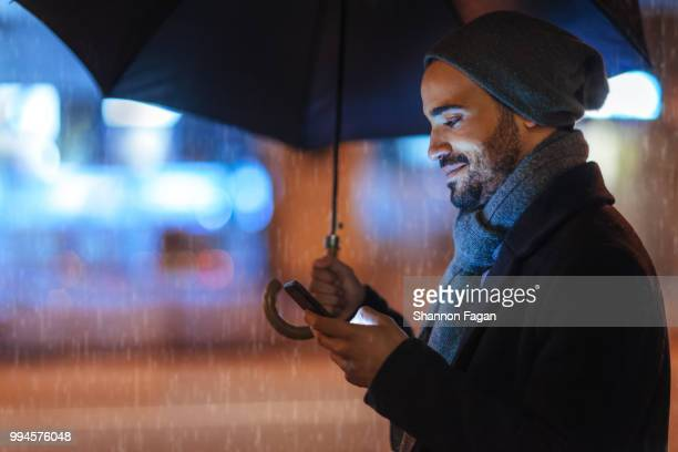 street portrait of a young man holding mobile phone on a rainy day - umbrella stock photos and pictures