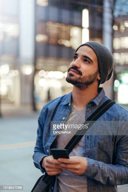street portrait of a young man holding mobile phone - southern european descent stock pictures, royalty-free photos & images