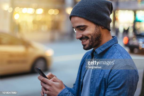 street portrait of a young man holding mobile phone - car pooling stock photos and pictures