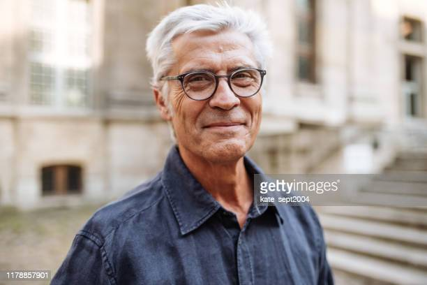 street portrait of smiling  senior man - senior adult stock pictures, royalty-free photos & images
