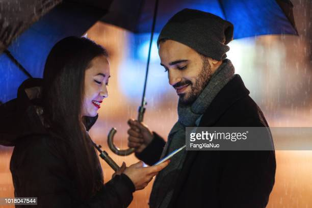 street portrait of young couples on a rainy day - winter coat stock pictures, royalty-free photos & images