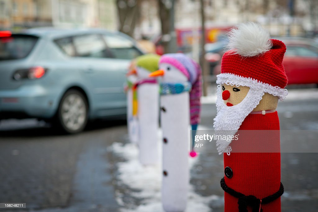 Street posts are decorated with knitted figures of snowmen and Santa Claus in front of a knit accessories shop in Bamberg, southern Germany, on December 11, 2012.