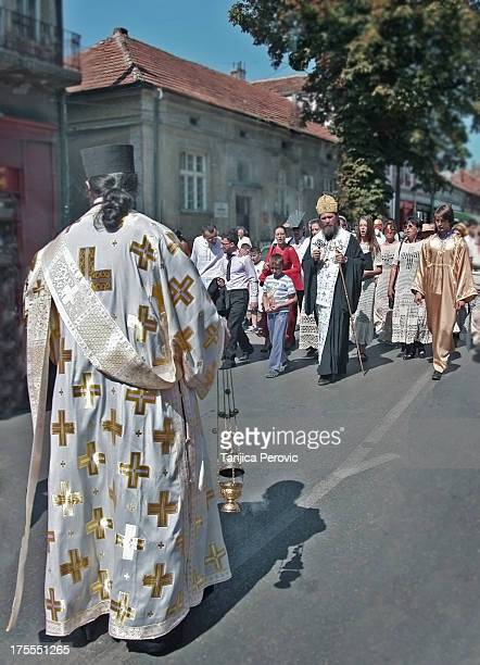 CONTENT] Street Procession on the day of town feast of the Dormition or Ascension of Mother of God with a deacon wearing orarion and holding censer...