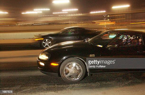 Street racers take off at the RaceLegalcom drag race at Qualcomm Stadium December 13 2002 in San Diego California Illegal street racing claims...