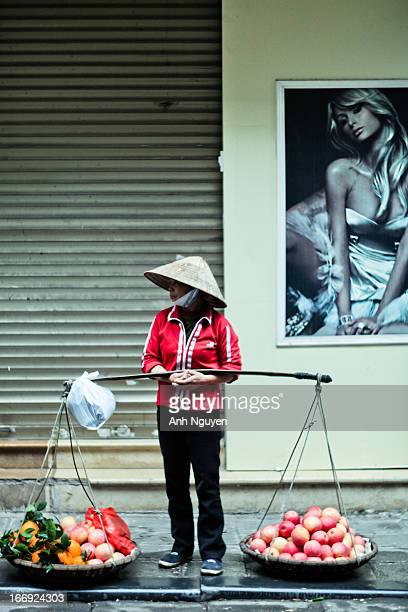 Street salesman of fresh fruits in conical hat standing against the wall with a modern fashionable poster in historical quarter of Hanoi, Vietnam.