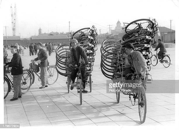 A street scene as bicyclist transport bicycles on their rickshaws in Peking China