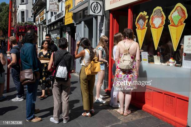 Street scene as people queue up outside an ice cream parlour and dessert shop in Chinatown in Soho London United Kingdom The present Chinatown is in...