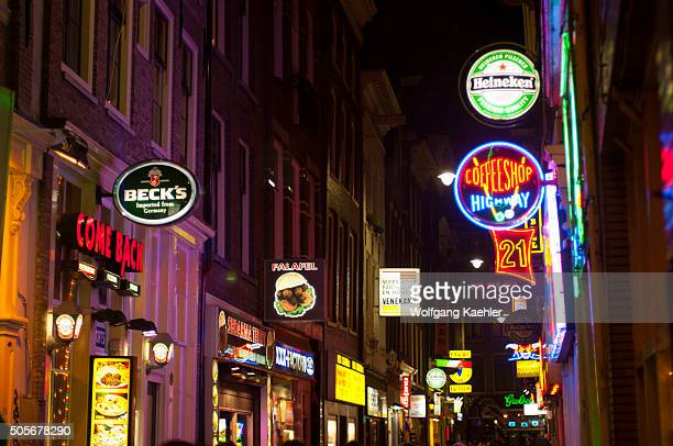 A street scene at night with a coffee shop and colorful neon signs in the red light district of Amsterdam in the Netherlands