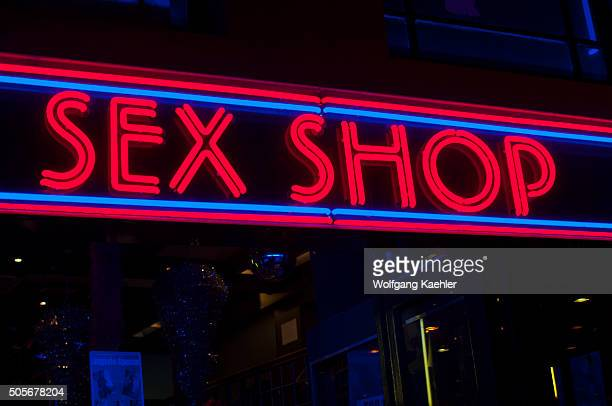 A street scene at night with a sex shop neon sign in the red light district of Amsterdam in the Netherlands
