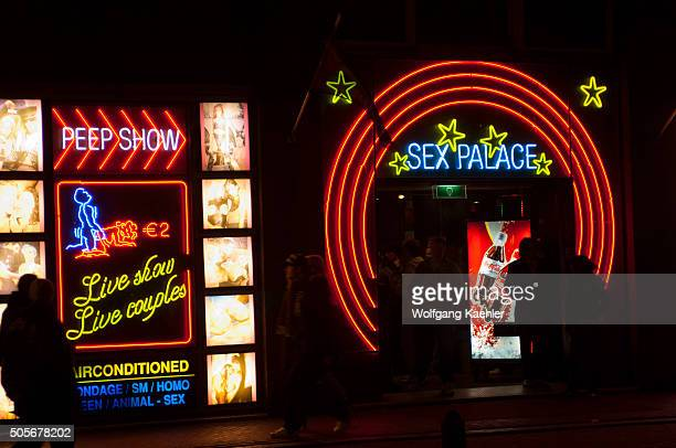 A street scene at night with colorful neon signs of a sex shop in the red light district of Amsterdam in the Netherlands