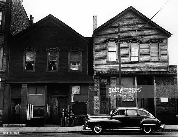 Street scene in an unidentified Chicago neighborhood shows three young children standing in front of a woodsided home with an automobile parked on...