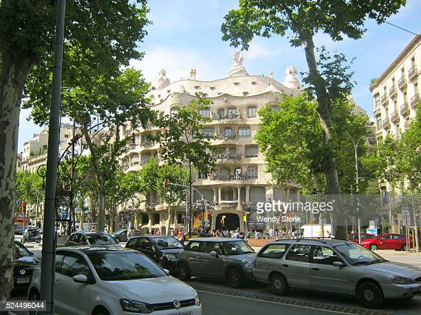 Street scene in Barcelona Spain focusing on Casa MIla Casa Mila was designed and constructed by Antoni Gaudi