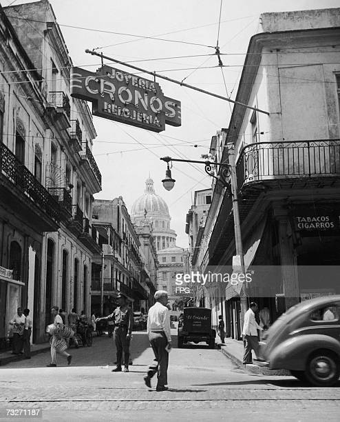 A street scene in Havana with the dome of the government building El Capitolio in the background 1950s